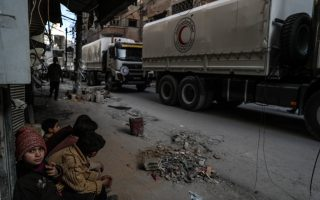 epaselect epa06583589 Children sit and watch a convoy of Syrian Arab Red Crescent (SARC)  trucks as they arrive in Douma, in Eastern Ghouta, Syria, 05 March 2018. Aid supplies reach the besieged community in Eastern Ghouta for the first time in weeks and after months of bombardment. The convoy contained food aid but many medical supplies were blocked by the Syrian regime.  EPA/Mohammed Badra