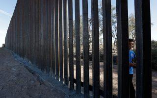 Ενα αγόρι  κοιτάζει μέσα από το πρώτο τμήμα του τείχους που θα χωρίζει το Καλέξικο της Καλιφόρνιας από το Μεξικάλι του Μεξικού.