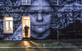 Βγαλμένη κομμάτι κομμάτι από τον φορητό φωτογραφικό εκτυπωτή του JR, η εικόνα μιας καθημερινής γυναίκας καταλαμβάνει τον τοίχο του σπιτιού της.