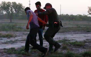 Συνοριακός φρουρός συλλαμβάνει μετανάστες που πέρασαν παράνομα τα σύνορα ΗΠΑ - Μεξικού κοντά στο Μακάλεν στο Τέξας.