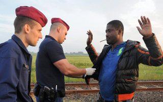 Ούγγροι αστυνομικοί ελέγχουν τα έγγραφα Αφρικανού μετανάστη στα σύνορα Ουγγαρίας - Σερβίας, το 2015.