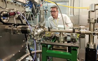 Ο καθηγητής Τζον Μακ Γκίχαν του Πανεπιστημίου του Πόρτσμουθ στέκεται πλάι στο όργανο που χρησιμοποιήθηκε για να αποκαλύψει την ατομική δομή του ενζύμου που «καταβροχθίζει» πλαστικά.