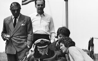 O πρώην πρωθυπουργός του Ηνωμένου Βασιλείου, Σερ Ουίνστον Τσόρτσιλ, χαιρετάει τη Νέα Υόρκη με τον χαρακτηριστικό χαιρετισμό της νίκης («V sign»), σηκώνοντας τον δείκτη και τον μέσο του δεξιού του χεριού, καθώς εισέρχεται στον ποταμό Χάντσον, πάνω στη θρυλική θαλαμηγό «Χριστίνα» του Έλληνα κροίσου και φίλου του, Αριστοτέλη Ωνάση, το 1961. Ο συγκεκριμένος χαιρετισμός υπήρξε χαρακτηριστικός για τον πρώην Βρετανό πρωθυπουργό κατά τη διάρκεια του Β' Παγκοσμίου Πολέμου, καθώς τον έκανε δημόσια σε διάφορες συγκυρίες την περίοδο 1940-45. (AP Photo)