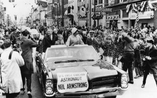 O θρυλικός Αμερικανός αστροναύτης Νηλ Άρμστρονγκ, τρία χρόνια πριν γίνει ο πρώτος άνθρωπος που πάτησε το πόδι του στη Σελήνη, γίνεται δεκτός με τιμές ήρωα στην ιδιαίτερη πατρίδα του, την πόλη Ουαπακονέτα του Οχάιο, κατά την επιστροφή του από την αποστολή Τζεμίνι 8, την πρώτη επιτυχημένη σύνδεση διαστημοπλοίων στον αέρα, το 1966. Μαζί του στο αυτοκίνητο επιβαίνουν η σύζυγος του, Ζαν, και ο γιος του, Έρικ. (AP Photo/Julian C. Wilson)