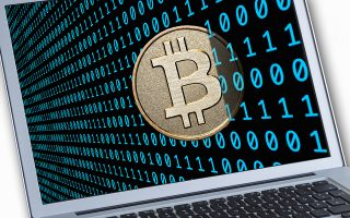 This is a visualization of a Bitcoin together with binary bode on a notebook display. Bitcoin (BTC) is a decentralized digital currency.