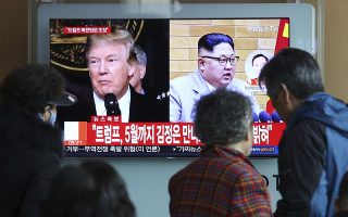 People watch a TV screen showing North Korean leader Kim Jong Un and U.S. President Donald Trump, left, at the Seoul Railway Station in Seoul, South Korea, Friday, March 9, 2018. Trump has accepted an offer of a summit from the North Korean leader and will meet with Kim Jong Un by May, a top South Korean official said Thursday, in a remarkable turnaround in relations between two historic adversaries. The signs read: