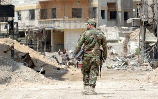 epa06661986 Syrian soldiers walk amongst destruction in the newly-captured town of Zamalka town, Eastern Ghouta, in the countryside of Damascus, Syria, 11 April 2018. The city was recently recaptured by the Syrian government during a military offensive that was launched more than a month ago against rebels. According to media reports, Syrian army seized control of scores of towns and villages in the area.  EPA/YOUSSEF BADAWI