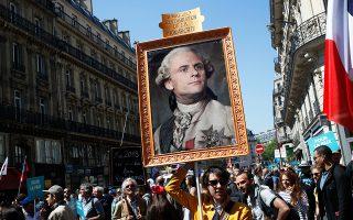 Διαδηλωτής κρατάει φωτογραφία του Μακρόν ως Λουδοβίκου ΙΣΤ΄ στη διάρκεια διαμαρτυρίας στο Παρίσι.