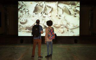 Λεπτομέρεια από την οπτικοακουστική βιντεο-εγκατάσταση «The Primary Fact» του Ιάπωνα εικαστικού Χικάρου Φουτζίι. Οι δύο επισκέπτες παρακολουθούν τμήμα του ομαδικού τάφου, με τους ογδόντα εκτελεσμένους ικέτες θαμμένους τον ένα πλάι στον άλλο.