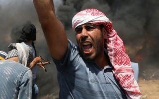 Παλαιστίνιος διαδηλωτής χρησιμοποιεί σφεντόνα στα σύνορα Γάζας - Ισραήλ.