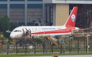 Εργάτες επιθεωρούν το αεροσκάφος της Sichuan Airlines στο οποίο έσπασε και αποκολλήθηκε ένας υαλοπίνακας του κόκπιτ.