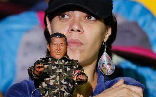 Ψηφοφόρος του Μαδούρο πανηγυρίζει τη νίκη του κρατώντας κούκλα με τη μορφή του Ούγκο Τσάβες.