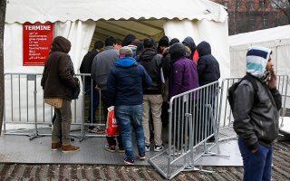Μετανάστες και πρόσφυγες περιμένουν έξω από το κέντρο αιτούντων άσυλο στο Βερολίνο.