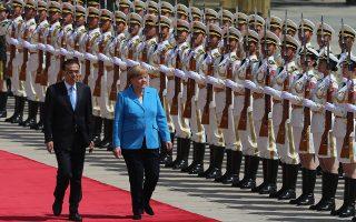 Η Μέρκελ και ο πρωθυπουργός της Κίνας Λι περνούν μπροστά από άγημα στο Πεκίνο.