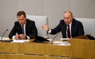 Russian President Vladimir Putin (R) and Dmitry Medvedev, who was confirmed as Prime Minister by the lower house of parliament, attend a session of the State Duma in Moscow Russia May 8, 2018. REUTERS/Sergei Karpukhin
