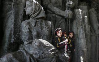 Απεικόνιση του πολέμου. Στο τεράστιο άγαλμα με το κορίτσι που κρατά στην αγκαλιά του μια βόμβα, ξαπόστασαν οι πιτσιρικάδες μετά την πρόβα της παρέλασης για την επέτειο της νίκης της Ουκρανίας στον Β' Παγκόσμιο Πόλεμο στις 9 Μαίου. Νίκη, που γιορτάζουν όλες οι χώρες που ανήκαν στην πρώην Σοβιετική Ενωση.   EPA/SERGEY DOLZHENKO