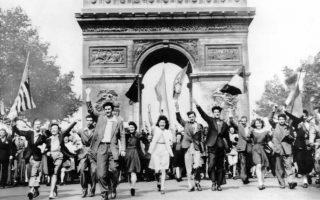 Πολίτες όλων των ηλικιών πανηγυρίζουν μπροστά από την Αψίδα του Θριάμβου, στο Παρίσι, για την άνευ όρων παράδοση της ναζιστικής Γερμανίας στους Συμμάχους, κραδαίνοντας σημαίες των συμμαχικών χωρών, το 1945. Την προηγούμενη μέρα, η γερμανική στρατιωτική ηγεσία υπέγραψε την παράδοση του Τρίτου Ράιχ στην πόλη Ρενς της βόρειας Γαλλίας. (AP Photo)