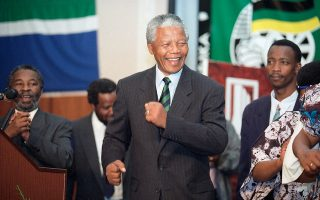 Ο ηγέτης του Αφρικανικού Εθνικού Κογκρέσου, Νέλσον Μαντέλα, πανηγυρίζει χορεύοντας, καθώς έχει ανέβει στο βήμα από το οποίο θα δώσει την ιστορική ομιλία του για τη νίκη του στις εθνικές εκλογές της 26ης - 29ης Απριλίου και την εκλογή του στο προεδρικό αξίωμα της Νότιας Αφρικής, στο Γιοχάνεσμπουργκ, το 1994. (AP Photo/David Brauchli)