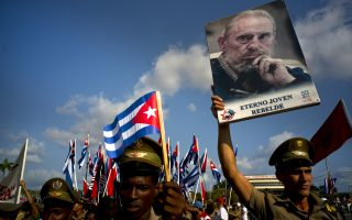 Cuban soldiers, some holding national flags and one holding a poster that depicts the late Cuban leader Fidel Castro with a message that reads in Spanish: