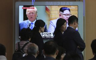 People pass by a TV screen showing file footage of U.S. President Donald Trump, left, and North Korean leader Kim Jong Un during a news program at the Seoul Railway Station in Seoul, South Korea, Friday, May 18, 2018. South Korea said Friday it believes North Korea remains committed to improving relations despite strongly criticizing Seoul over ongoing U.S.-South Korean military drills and insisting it will not return to inter-Korean talks unless its grievances are resolved. (AP Photo/Ahn Young-joon)