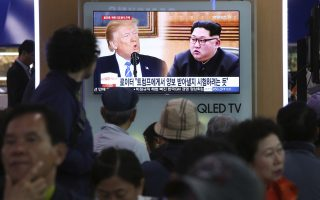 People watch a TV screen showing file footage of U.S. President Donald Trump, left, and North Korean leader Kim Jong Un during a news program at the Seoul Railway Station in Seoul, South Korea, Wednesday, May 16, 2018. North Korea on Wednesday threatened to scrap a historic summit next month between its leader, Kim Jong Un, and U.S. President Donald Trump, saying it has no interest in a