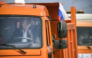 epa06738690 Russian President Vladimir Putin drives a KamAZ truck at the head of a truck convoy crossing the road-and-rail Krymsky (Crimean) Bridge over the Kerch Strait, Crimea, 15 May 2018. Vladimir Putin inaugurated the 19-kilometers-long road-and-rail bridge that connects the Crimean peninsula, annexed by Russia from Ukraine in March 2014, with the Taman Peninsula of the Russian mainland. Public transport and automobiles traffic on Crimean Bridge will be launched in early hours of 16 May 2018.  EPA/ALEXANDER NEMENOV/POOL