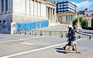 Τουρίστες στην καλοκαιρινή Αθήνα παρατηρούν ένα γκράφιτι στην Αθηναϊκή Τριλογία: «Για πάντα ένα δάνειο». Η ευρωπαϊκή νεολαία είδε τα ερείπια της σύγχρονης Αθήνας ως έναν τεράστιο καμβά για γκράφιτι (γκραφιτοτουρισμός).