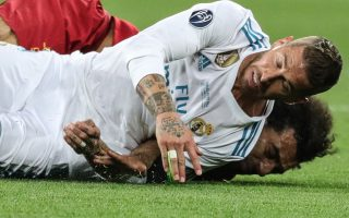 epa06766187 Mohamed Salah (back) of Liverpool and Sergio Ramos of Real Madrid fall during the UEFA Champions League final between Real Madrid and Liverpool FC at the NSC Olimpiyskiy stadium in Kiev, Ukraine, 26 May 2018. The incident let to an injury of Salah who was shortly after taken off the pitch.  EPA/ARMANDO BABANI
