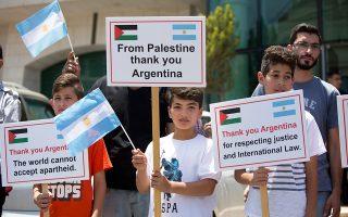 Mικροί Παλαιστίνιοι ευχαριστούν την Αργεντινή με πλακάτ μπροστά από το γραφείο της αντιπροσωπείας της, στη Ραμάλα.