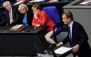 Ο γραμματέας της κοινοβουλευτικής ομάδας της Εναλλακτικής για τη Γερμανία Μπερντ Μπάουμαν μιλάει δίπλα στην καγκελάριο Αγκέλα Μέρκελ και στον Γερμανό υπουργό Εσωτερικών Χορστ Ζεεχόφερ.
