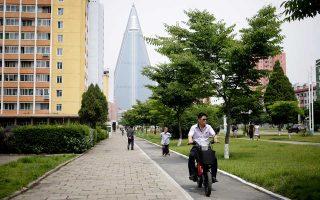 Ενας άνδρας με μηχανή περνάει μπροστά από την πυραμίδα 105 ορόφων στην Πιονγιάνγκ.