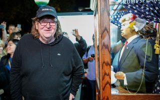 Ο Μάικλ Μουρ περνάει χαμογελώντας δίπλα από ένα ομοίωμα του Ντόναλντ Τραμπ.