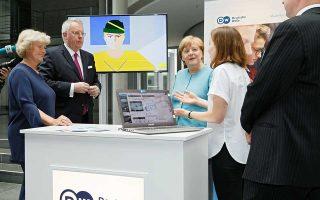Η υφυπουργός Πολιτισμού και ΜΜΕ της Γερμανίας Μόνικα Γκρίτερς, ο γενικός διευθυντής της Deutsche Welle Peter Limbourg και η Γερμανίδα καγκελάριος Αγκελα Μέρκελ στο σταντ πληροφοριών του πρακτορείου, στη γιορτή για τα 65 χρόνια παρουσίας.