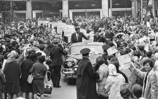 Κρατώντας αμερικανικές σημαίες και ζητωκραυγάζοντας, πλήθος κόσμου υποδέχεται την αυτοκινητοπομπή που μεταφέρει τον Αμερικανό πρόεδρο Τζον Φιτζέραλντ Κένεντι, τον μοναδικό καθολικό πρόεδρο στην ιστορία των Ηνωμένων Πολιτειών, στο Κορκ της Ιρλανδίας, το 1963. (AP Photo)