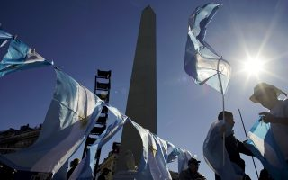 A vendor sells national flags near the Obelisk monument, in Buenos Aires, Argentina, Friday, May 25, 2018. Thousands of people protested against the government's decision to seek economic help from the International Monetary Fund. (AP Photo/Victor R. Caivano)