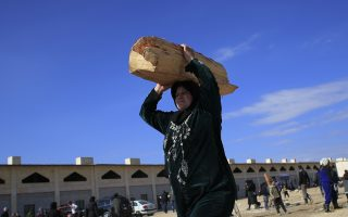 A woman displaced with her family from eastern Aleppo holds a log of wood in the village of Jibreen south of Aleppo, Syria, Saturday, Jan. 21, 2017. (AP Photo/Hassan Ammar)