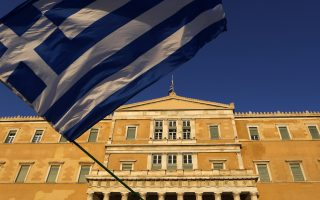 A pro-Euro demonstrator waves a Greek flag in front of the Greek Parliament during a rally at Syntagma square in Athens, Thursday, July 9, 2015. Greece's government is racing to finalize a plan of reforms for its third bailout, hoping this time the proposal will meet with approval from its European partners and stave off a potentially catastrophic exit from Europe's joint currency, the euro, within days. (AP Photo/Petros Karadjias)