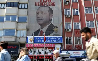 epa06679392 People walking under a huge picture of Turkish President Recep Tayyip Erdogan in Istanbul, Turkey, 19 April 2018. The presidental and parliamentary elections were scheduled to be held in November 2019, but government has decided the change the date following the recommendation of the Nationalist Movement Party (MHP) leader Devlet Bahceli.  EPA/ERDEM SAHIN