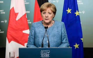epa06796873 German Chancellor Angela Merkel gives a media statement prior to her departure from the G7 summit in Charlevoix in Canada 09 June 2018. The G7 Summit runs from 8 to 9 June in Charlevoix, Canada.  EPA/CLEMENS BILAN