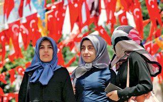 Τρεις γυναίκες περπατούν κάτω από μία σειρά σημαιών της Τουρκίας και διαφόρων κομμάτων, σε κεντρική πλατεία της Κωνσταντινούπολης. Οι εκλογές της Κυριακής είναι εξαιρετικής σημασίας, καθώς θα σηματοδοτήσουν τη μετατροπή του πολιτεύματος σε εκτελεστική προεδρία.