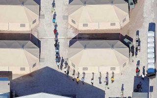 Παιδιά μεταναστών, πολλά εκ των οποίων έχουν αποχωριστεί τους γονείς τους με βάση την πολιτική του Τραμπ περί μηδενικής ανοχής, περπατούν στον καταυλισμό τους στο Τέξας, στα σύνορα με το Μεξικό.