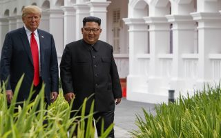 U.S. President Donald Trump walks with North Korea leader Kim Jong Un after lunch at the Capella resort on Sentosa Island Tuesday, June 12, 2018 in Singapore. (AP Photo/Evan Vucci)