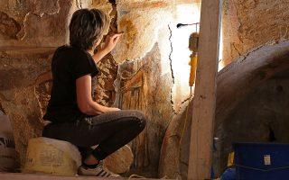 Η συντηρήτρια της Εφορείας Αρχαιοτήτων Κυκλάδων ανεβασμένη στη σκαλωσιά καθαρίζει με το νυστέρι, σιγά σιγά, την τοιχογραφία. (Φωτογραφία: Νίκος Κοκκαλιάς)