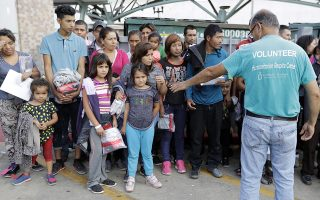 Immigrants are helped by a volunteer at the bus station after they were processed and released by U.S. Customs and Border Protection, Friday, June 22, 2018, in McAllen, Texas. (AP Photo/David J. Phillip)