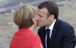 French President Emmanuel Macron, right, is welcomed by German Chancellor Angela Merkel before they visit the reconstruction site of the Berlin Palace in Berlin, Germany, Thursday, April 19, 2018. (AP Photo/Markus Schreiber)