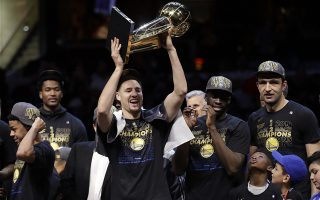 Golden State Warriors' Klay Thompson celebrates hols up the trophy after the Warriors defeated the Cleveland Cavaliers 108-85 in Game 4 of basketball's NBA Finals to win the NBA championship, Friday, June 8, 2018, in Cleveland. (AP Photo/Tony Dejak)