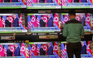 A man watches TV screens showing U.S. President Donald Trump, right, meeting with North Korean leader Kim Jong Un in Singapore, during a news program In Hong Kong, Tuesday, June 12, 2018.  (AP Photo/Vincent Yu)