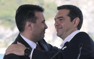 Greek Prime Minister Alexis Tsipras, right and his Macedonian counterpart Zoran Zaev, embrace during a signing of an agreement for Macedonia's new name in the village of Psarades, Prespes Greece, on Sunday, June 17, 2018. The preliminary deal launches a long process that will last several months. If successful, it will end a decades-long dispute between neighbors Greece and Macedonia _ which will be renamed North Macedonia. (AP Photo/Yorgos Karahalis)