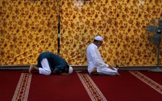 Pakistan Muslims offer the after-noon prayer while they observe
