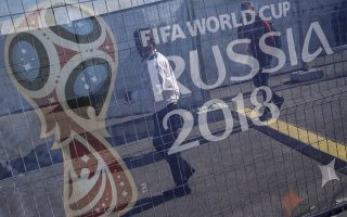 epa06807001 Two men are pictured through a banner on a gate showing the logo of the FIFA World Cup 2018 outside the Cosmos Arena in Samara, Russia, 14 June 2018.  The FIFA World Cup 2018 will take place in Russia from 14 June until 15 July 2018 across twelve different venues.  EPA/WALLACE WOON